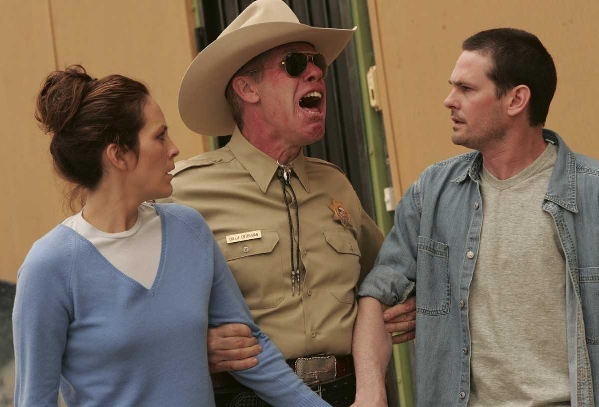 Annabeth Gish and Henry Thomas under arrest by possessed sheriff Ron Perlman in Desperation (2006)