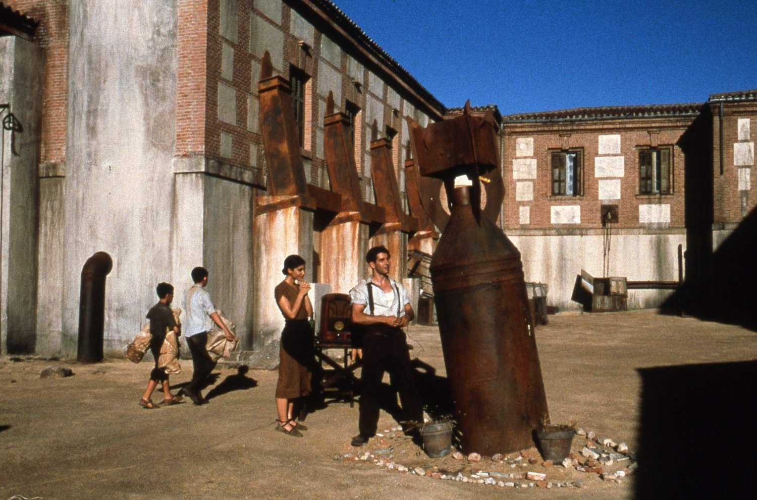 The unexploded bomb in the courtyard with Irene Visado and Eduardo Noriega standing next to it in The Devil's Backbone (2001)