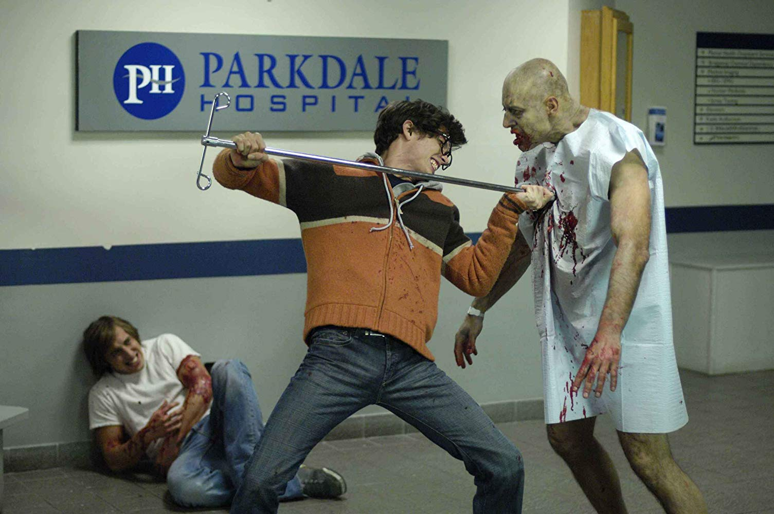 Joe Dinicol fights off a zombie while Chris Violette lies wounded in the background in Diary of the Dead (2007)