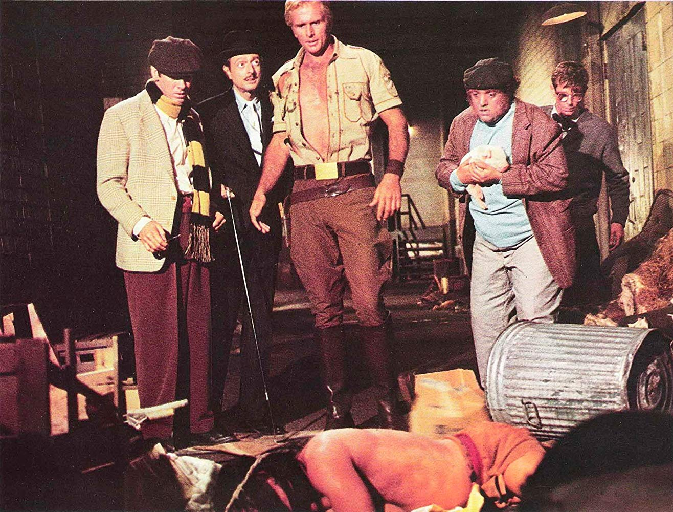 Doc and companions find a body - (l to r) Long Tom Roberts (Paul Gleason), Ham Brooks (Darrell Zwerling), Doc Savage (Ron Ely), Monk Mayfair (Michael Miller) and Johnny Littlejohn (Eldon Quick) in Doc Savage –The Man of Bronze (1975)