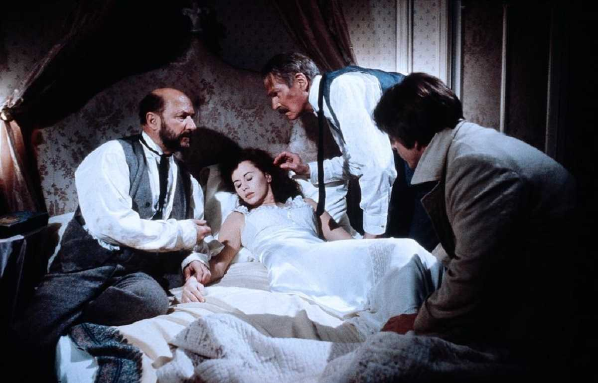 A bedridden Lucy Seward (Kate Neliigan) is tended by (l to r) Dr Seward (Donald Pleasence), Professor Van Helsing (Laurence Olivier) and Jonathan Harker (Trevor Eve) in Dracula (1979)