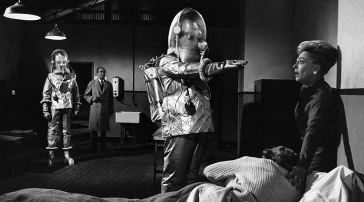 The invading alien robots threaten Vanda Godsell with a mind-controlled Dennis Price in the background in The Earth Dies Screaming (1964)