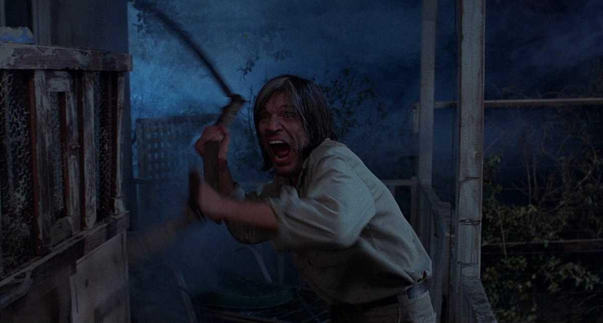 Mad scythe-wielding motelier Neville Brand in Eaten Alive (1977)