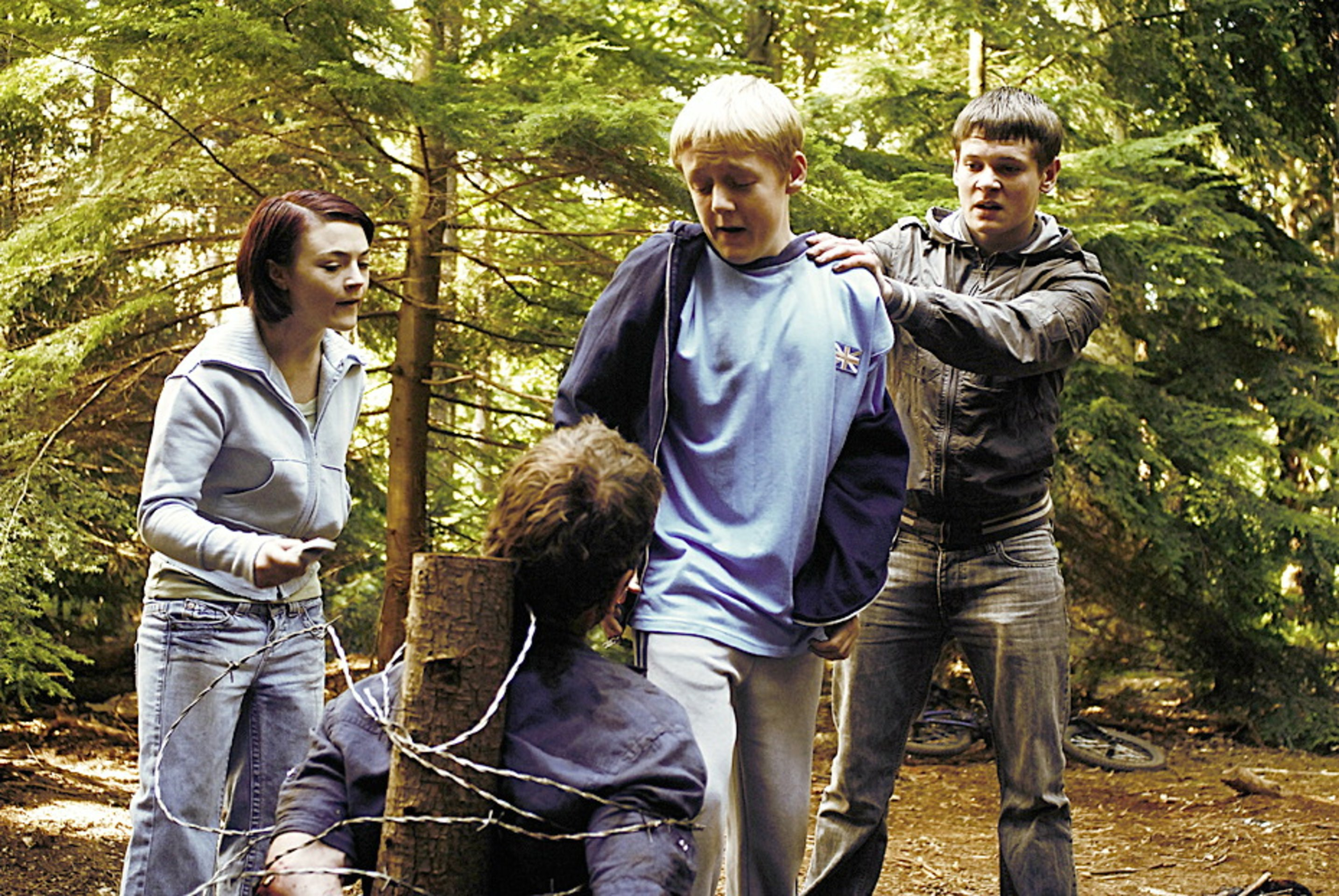 A bound Michael Fassbender is tortured by children - (l to r) Finn Atkins, Thomas Turgoose and Jack O'Connell) in Eden Lake (2008)