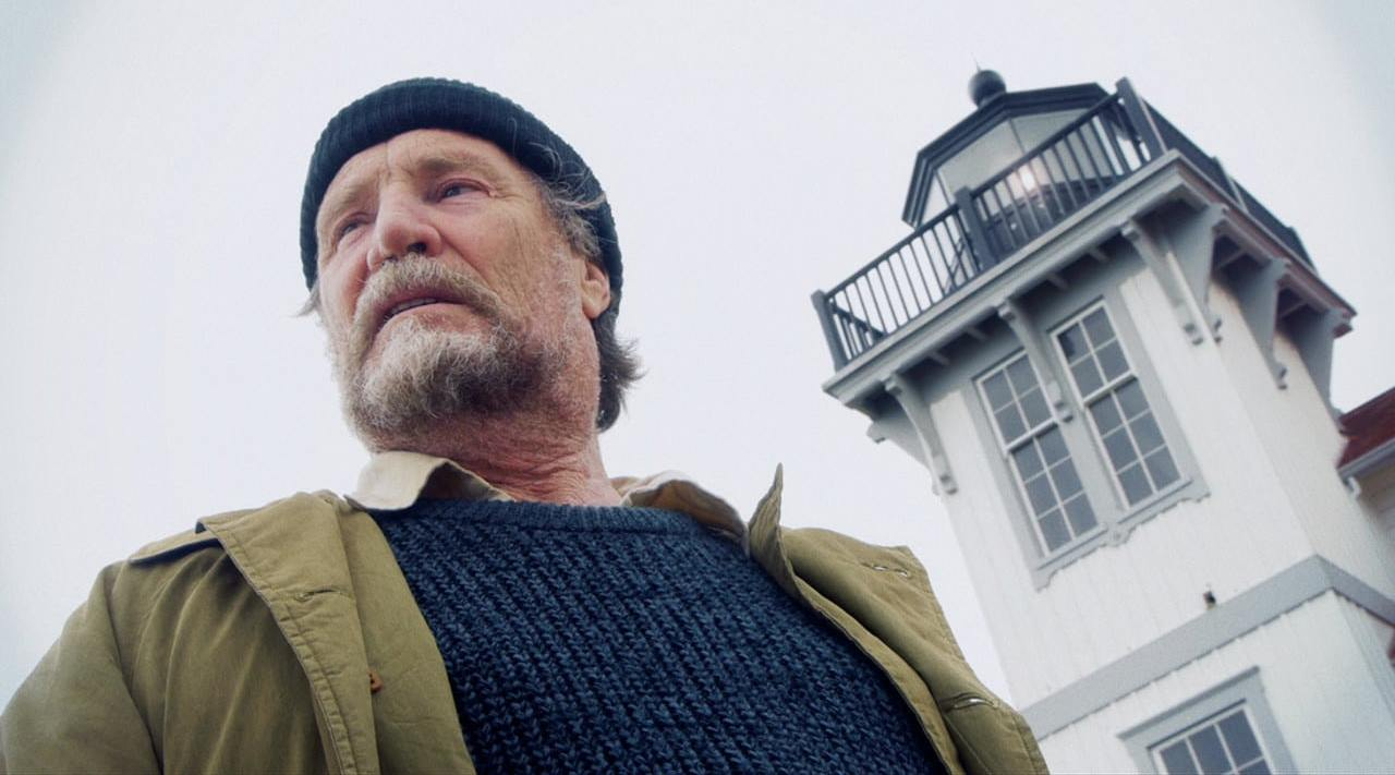 Vernon Wells as the lighthouse keeper alongside the lighthouse he tends in Edgar Allan Poe's Lighthouse Keeper (2016)