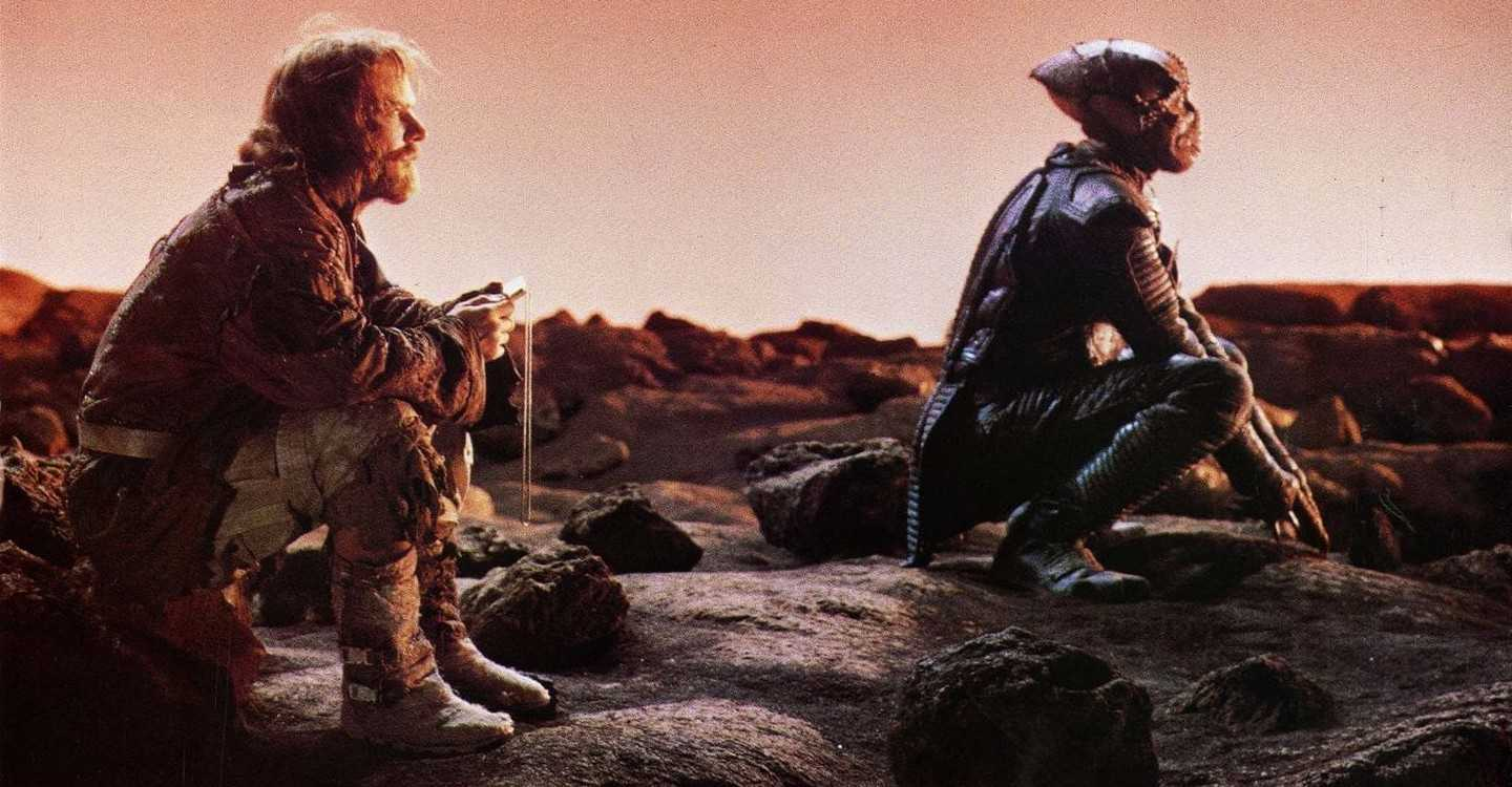 Human and alien enemies forced to cooperate for survival on a hostile planet - Davidge (Dennis Quaid) and Jeriba Shigan (Louis Gossett Jr) in Enemy Mine (1985)
