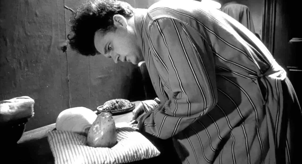 Henry (Jack Nance) left tending the baby in Eraserhead (1977)