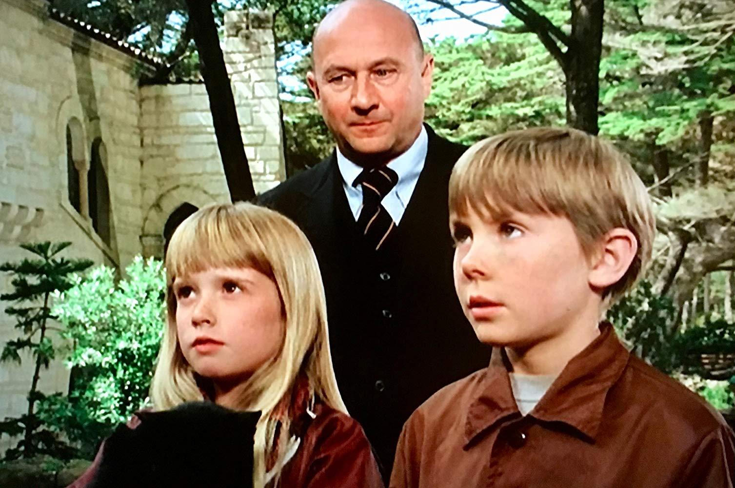 Psychically gitted alien children Tia (Kim Richards) and Tony (Ike Eisenmann) with pursuing henchman Lucas Derenian (Donald Pleasence) in the background in Escape to Witch Mountain (1975)