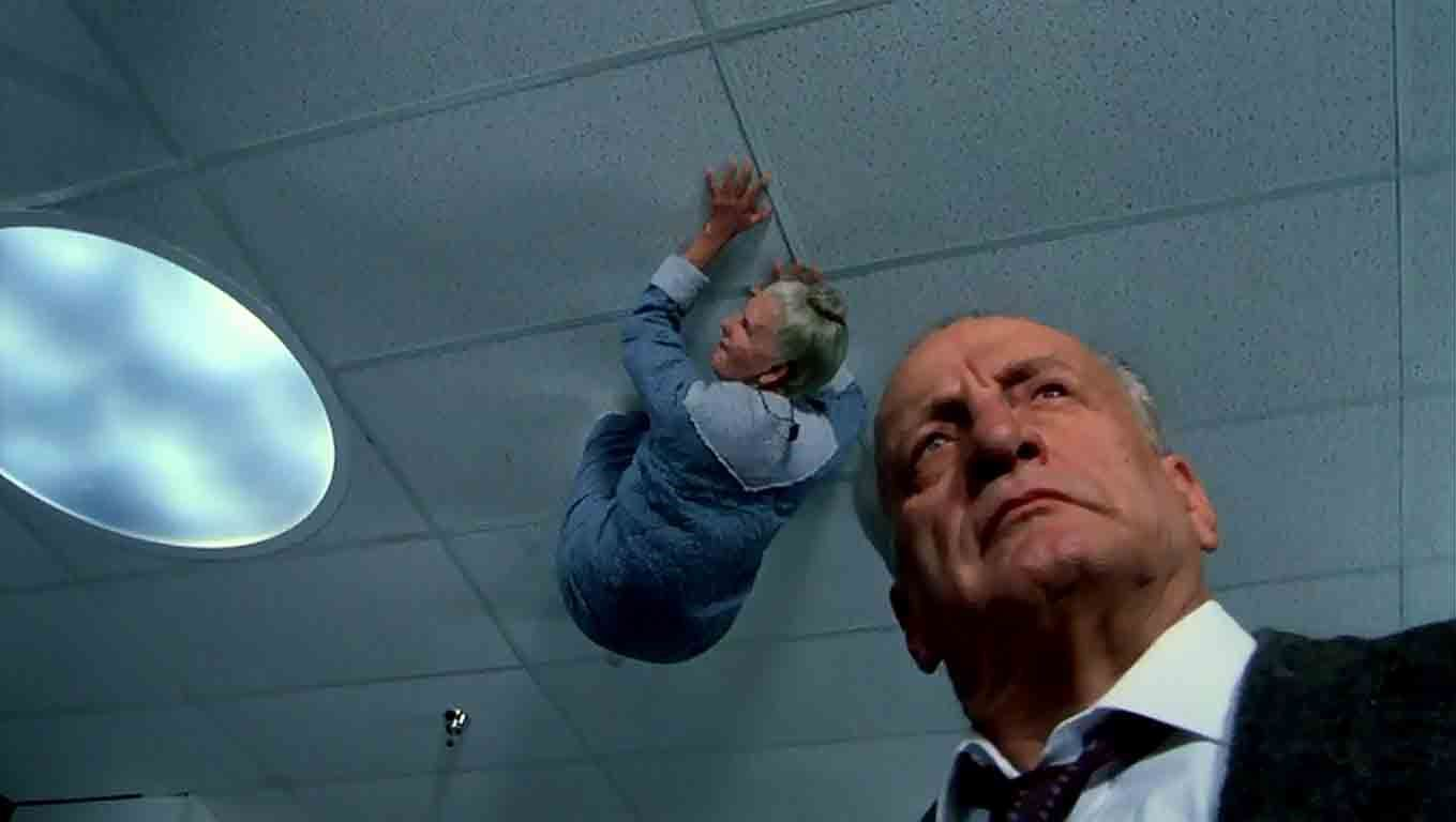 Lieutenant Kinderman (George C. Scott) investigates as seniors scuttle about on the ceiling in The Exorcist III (1990)