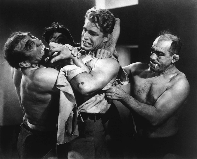 Flash Gordon (Larry 'Buster' Crabbe) battles the ape men in Flash Gordon (1936)