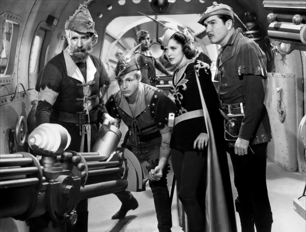 (l to r) Dr Zarkov (Frank Shannon), Flash Gordon (Larry 'Buster' Crabbe), Dale Arden (Carol Hughes) and Prince Barin (Roland Drew) in Flash Gordon Conquers the Universe (1940)