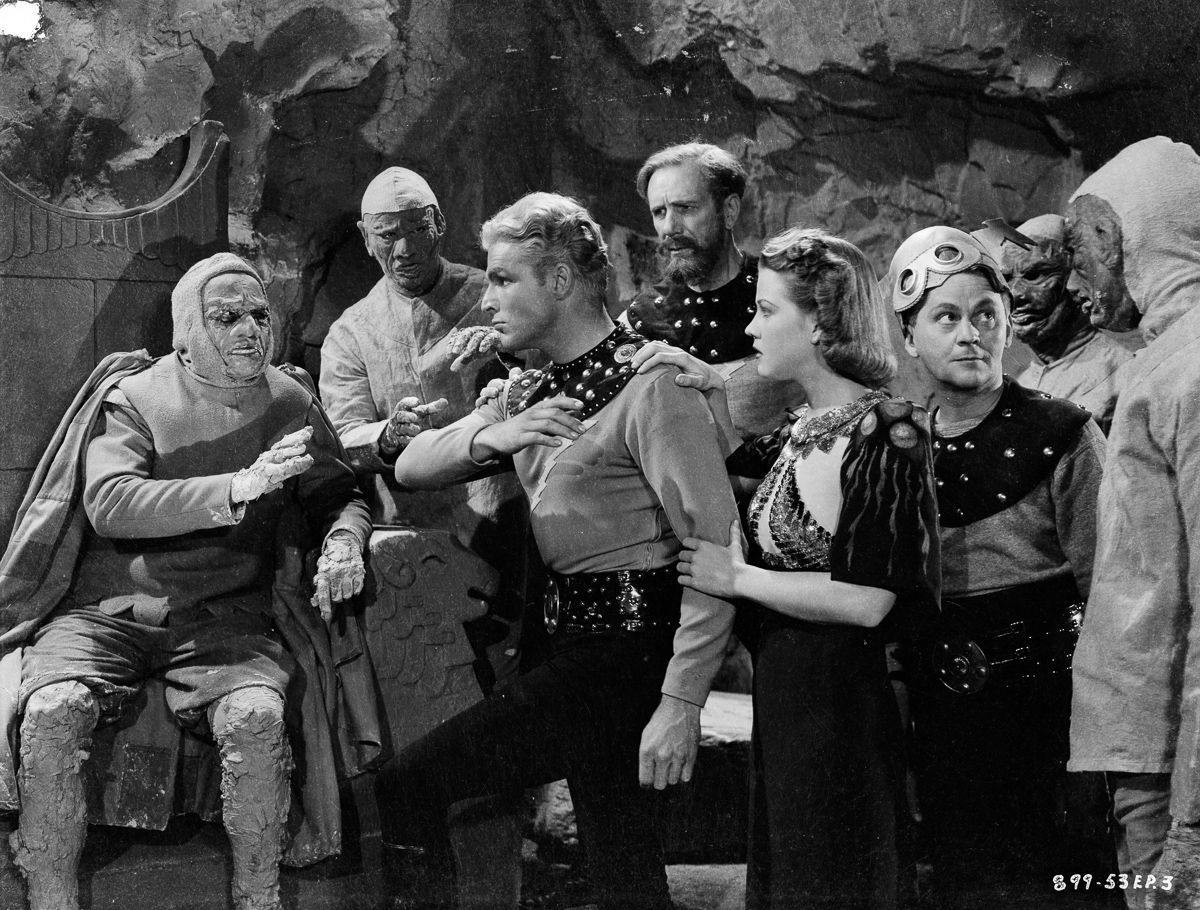 (l to r) Flash Gordon (Larry 'Buster' Crabbe), Dr Zarkov (Frank Shannon), Dale Arden (Jean Rogers) and comic relief Happy Hapgood (Donald Kerr) among the Clay People in Flash Gordon's Trip to Mars (1938)