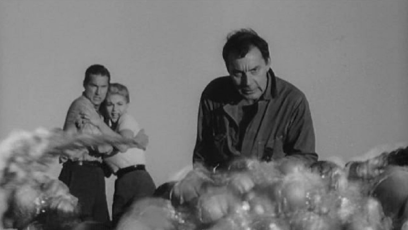 Nazi mad scientist Martin Kosleck examines the glowing slugs he has created while Byron Sanders protects Barbara Wilkin in The Flesh Eaters (1964)