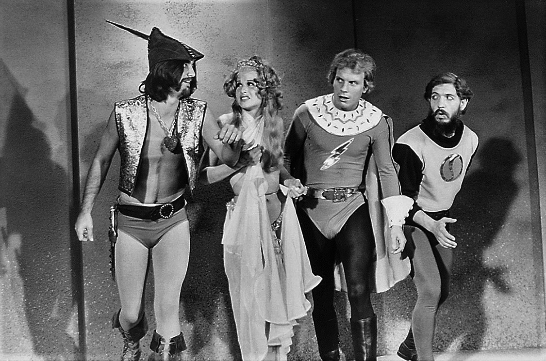 (l to r) Prince Precious (Lance Larsen), Dale Ardor (Suzanne Field), Flesh Gordon (Jason Williams) and Dr Flexei Jerkoff (Joseph Hudgins) in Flesh Gordon (1974)