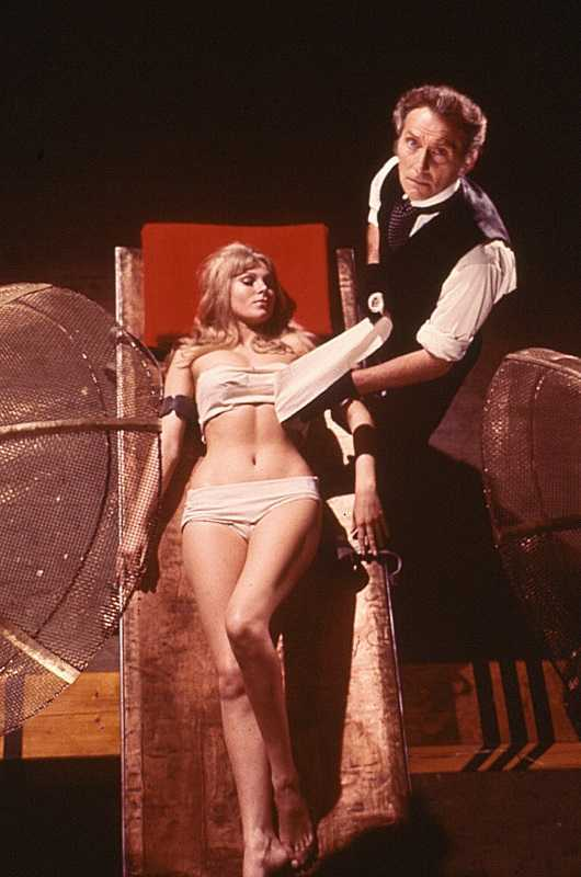 Baron Frankenstein (Peter Cushing) with an unconscious Susan Denberg on his laboratory table in Frankenstein Created Woman (1967)