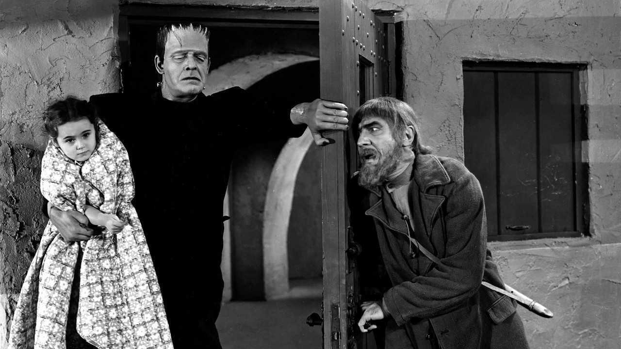 (l to r) The Frankenstein monster (Lon Chaney Jr) bursts in holding Janet Ann Gallow while Ygor (Bela Lugosi) waits behind the door in The Ghost of Frankenstein (1942)