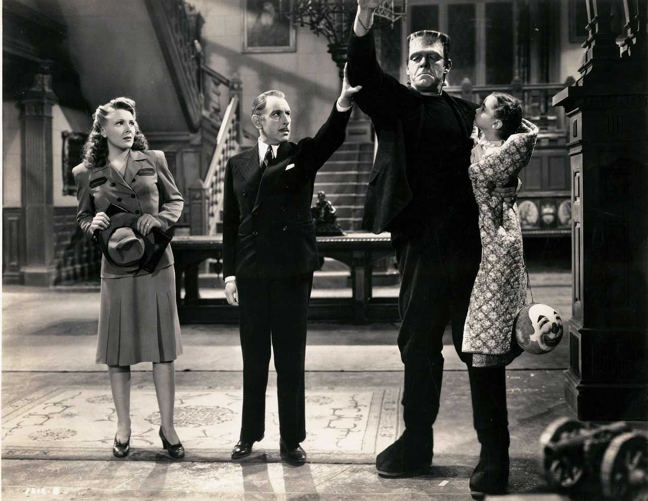 Ludwig Frankenstein (Cedric Hardwicke) accompanied by wife Elsa (Evelyn Ankers) introduces his monster (Lon Chaney Jr) holding Janet Ann Gallow in The Ghost of Frankenstein (1942)