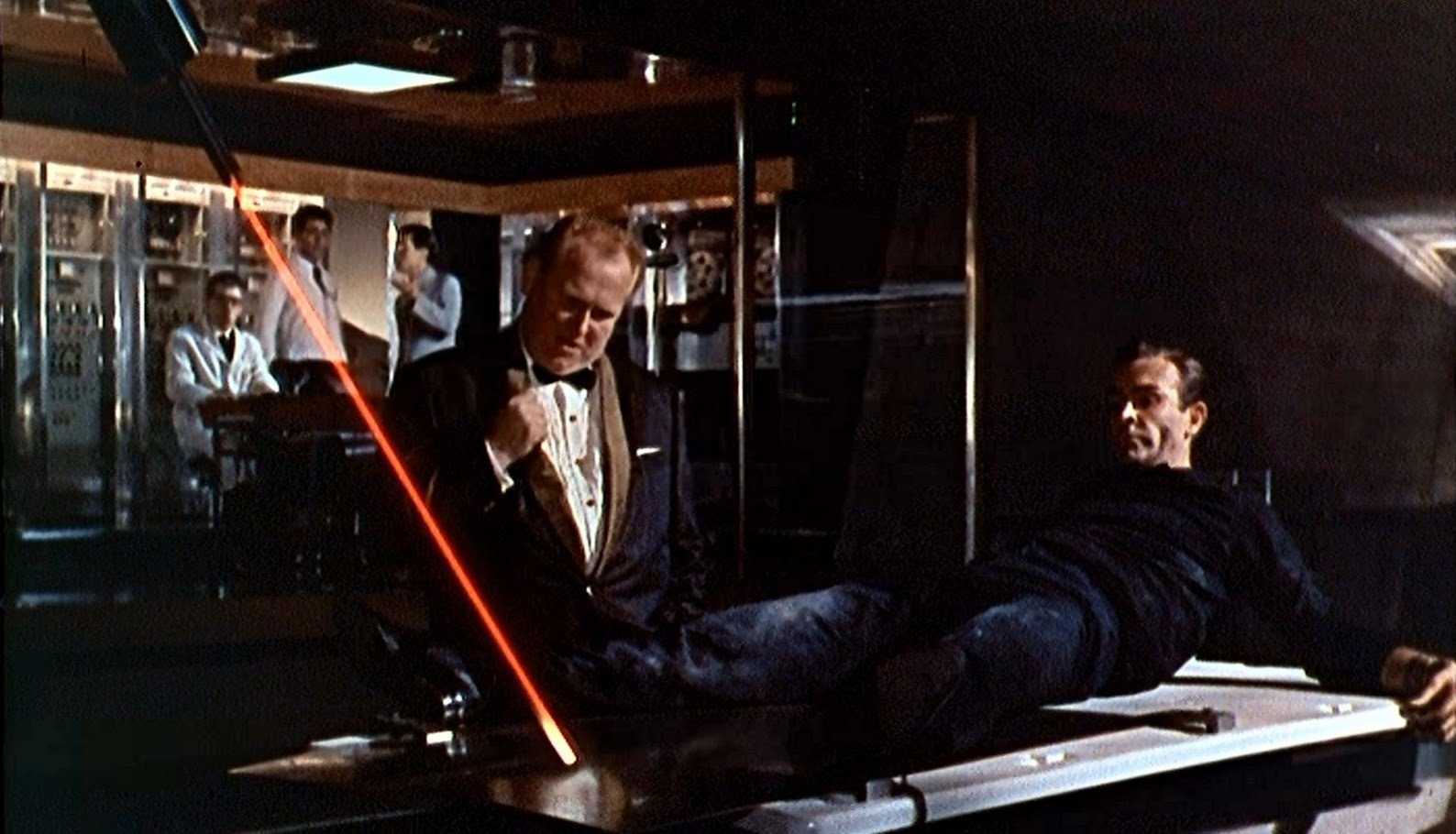 Goldfinger (Gert Frobe) with James Bond (Sean Connery) tied up in front of a laser in Goldfinger (1964)