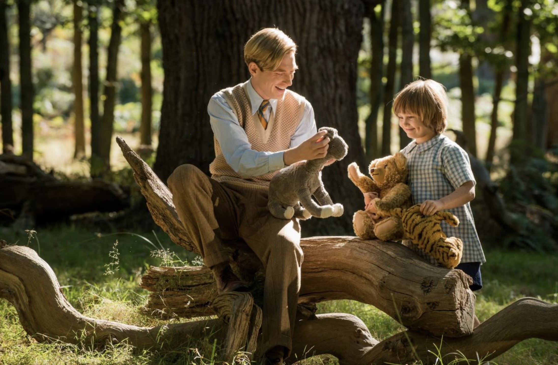 A.A. Milne (Domhnall Gleeson) and Christopher Robin (Will Tilston) play with the toys in Ashdown Woods in Goodbye Christopher Robin (2017)