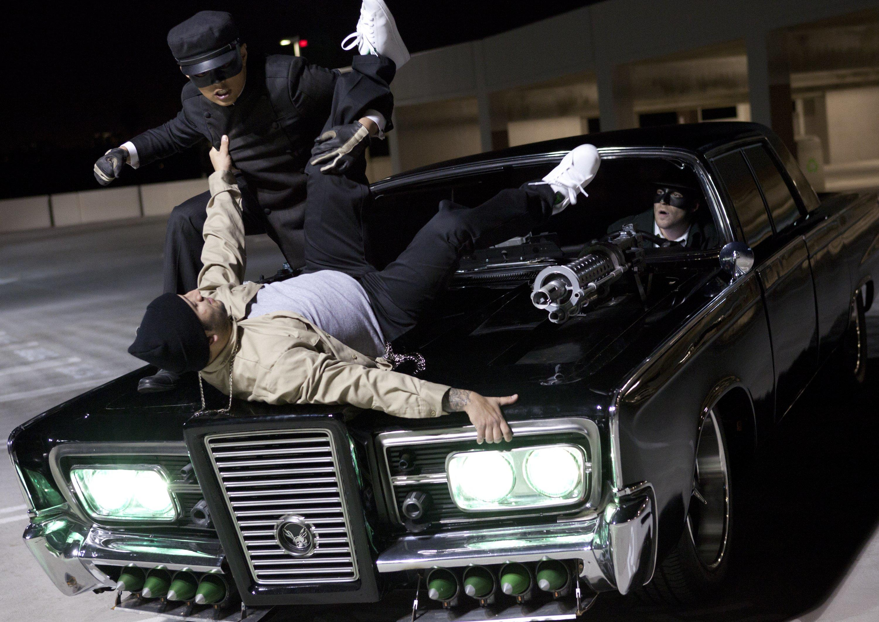 Kato (Jay Chou) stops a hoodlum atop the hood of Black Beauty with The Green Hornet (Seth Rogen) behind the wheel in The Green Hornet (2011)