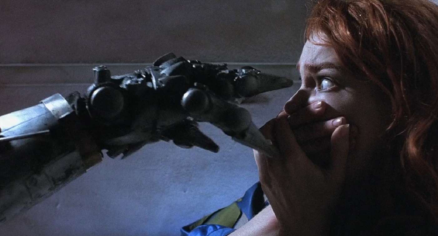 Stacey Travis under attack by a killer robot in Hardware (1990)