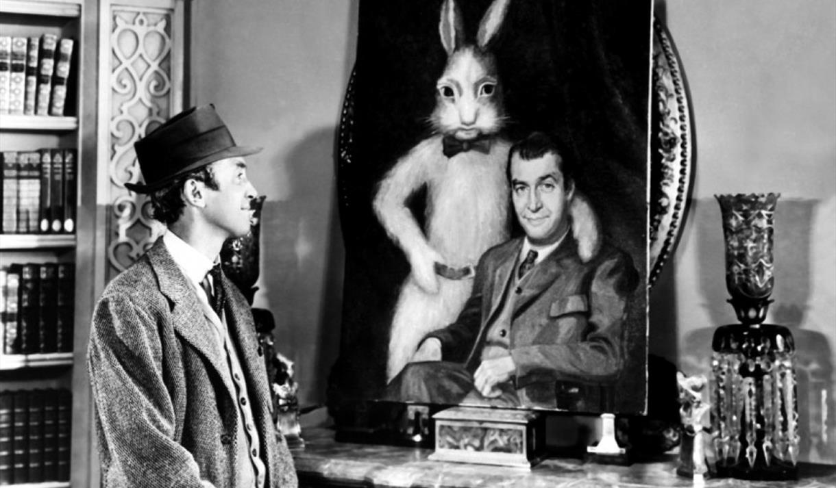 Elwood P. Dowd (James Stewart) looks affectionately on at the portrait of himself and Harvey in Harvey (1950)