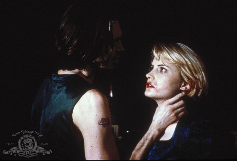 Steve Buscemi threatens Jennifer Jason Leigh in Heart of Midnight (1988)