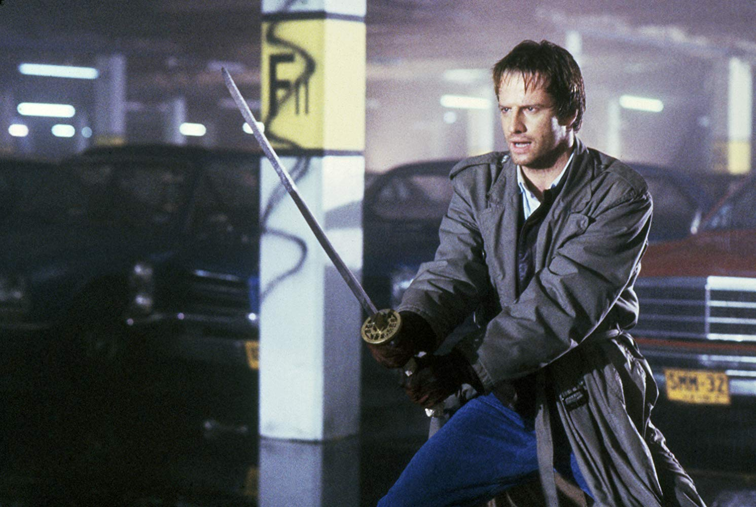 Connor McLeod (Christopher Lambert) enters a duel in a carpark building in Highlander (1986)