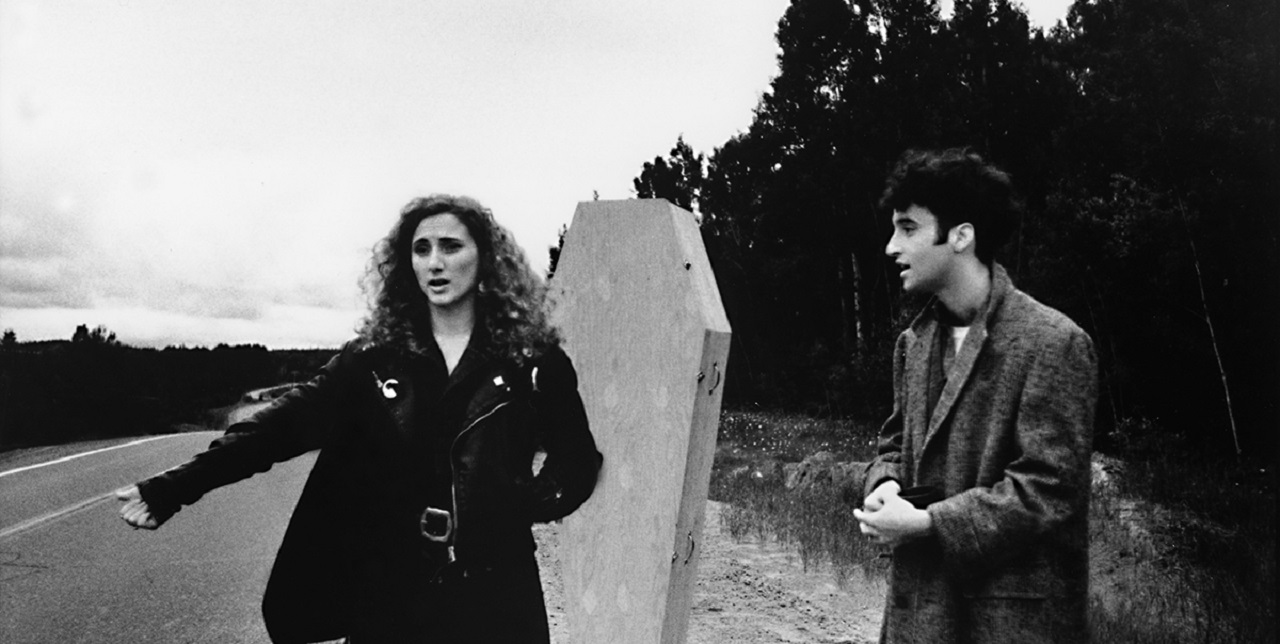 Valerie Buhagiar and Don McKellar go hitchhiking with a coffin in Highway 61 (1991)