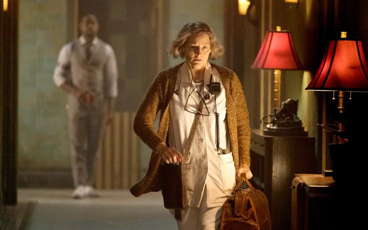 Jodie Foster as The Nurse with Waikiki (Sterling K. Brown) in the background in Hotel Artemis (2018)