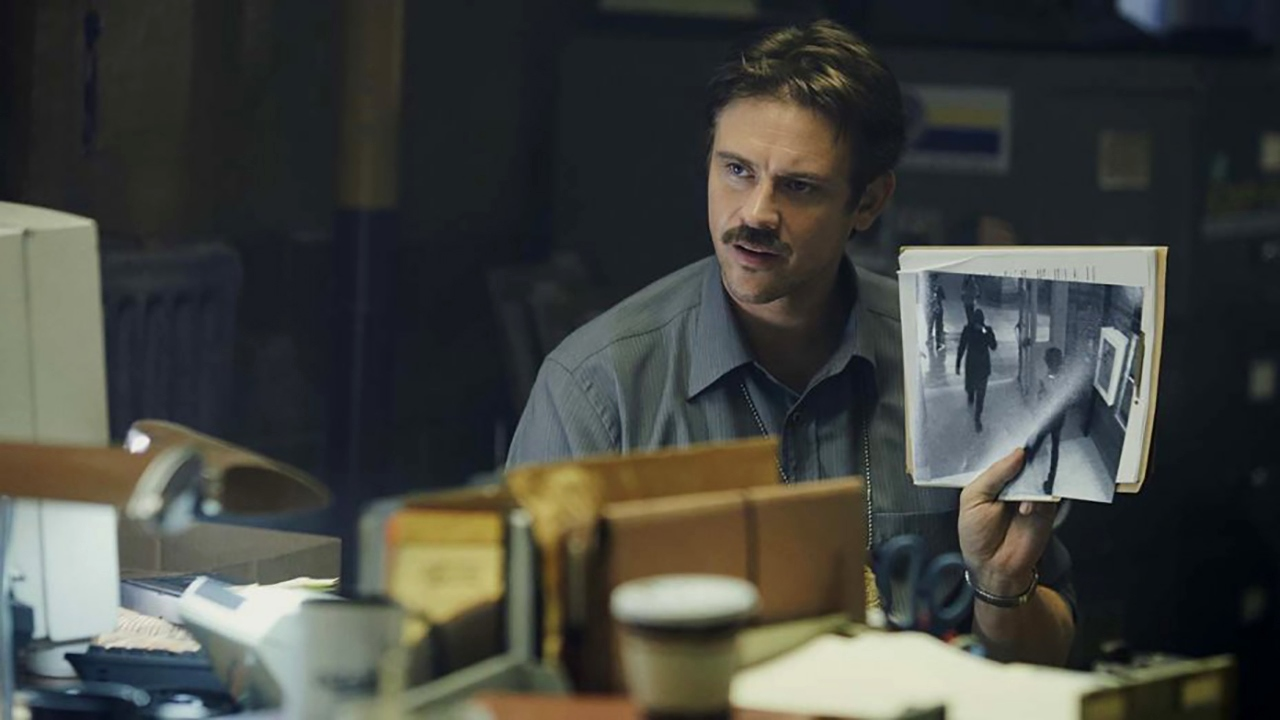 In 1997, detective Boyd Holbrook holds up a surveillance camera picture of mystery girl Cleopatra Coleman in In the Shadow of the Moon (2019)