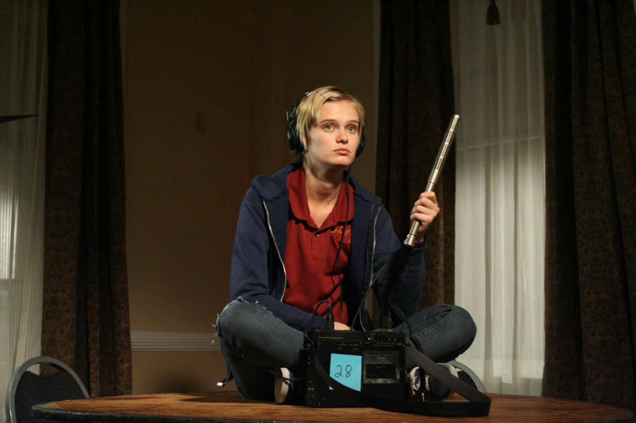 Sara Paxton sits listening with EVP equipment in The Innkeepers (2011)