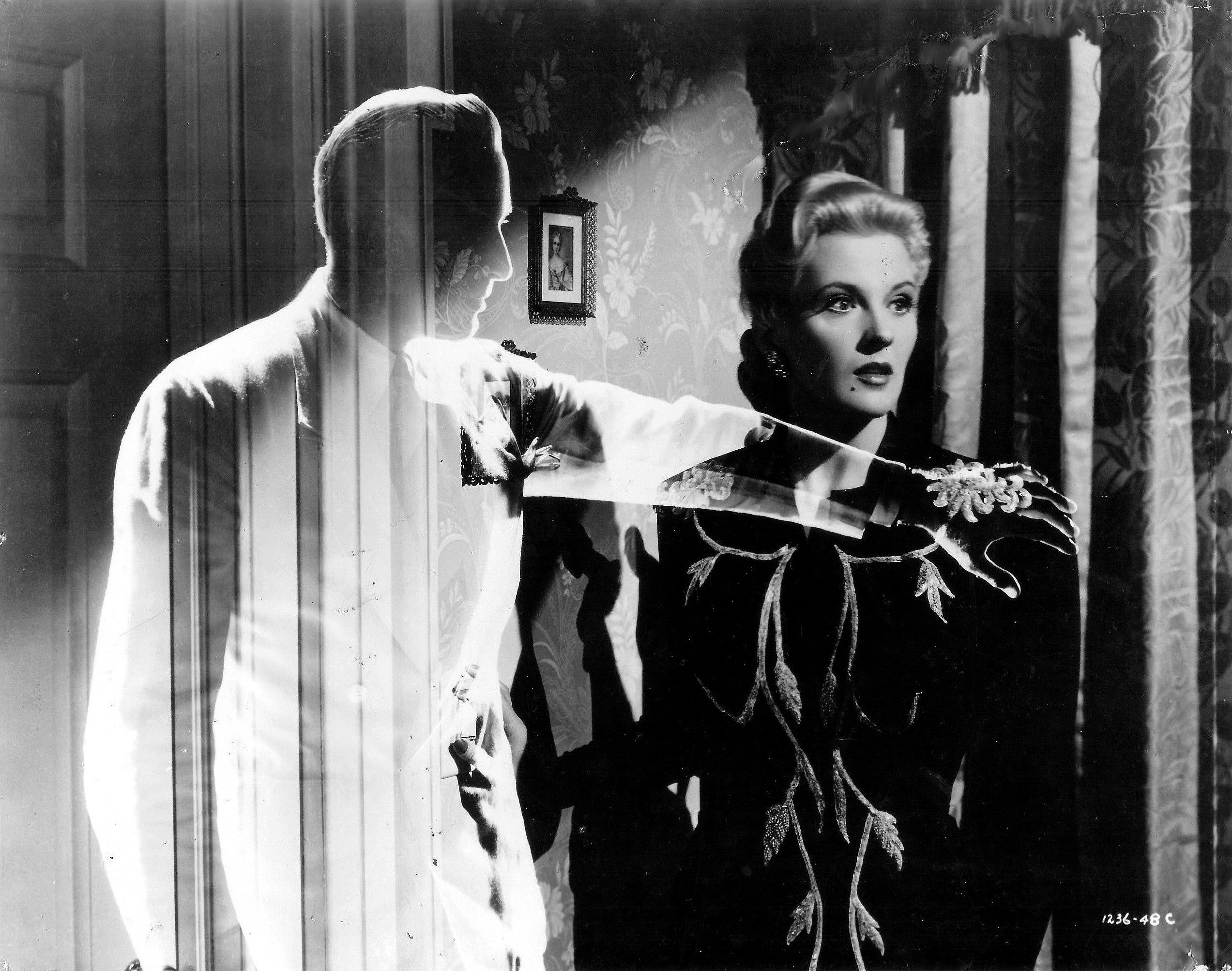 An invisible Jon Hall comforts Ilona Massey in Invisible Agent (1942)