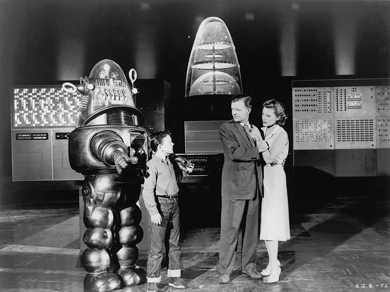 Robbie the Robot, young Richard Eyer and parents Phillip Abbott and Diane Brewster with Univac in the background in The Invisible Boy (1957)
