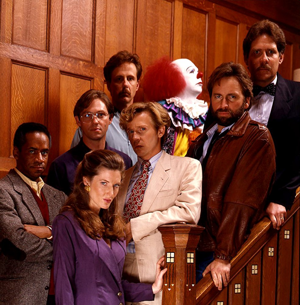 The grown-ups - (l to r) Tim Reid, Annette O'Toole, Richard Thomas, Harry Anderson, Dennis Christopher, Pennywise (Tim Curry), John Ritter, Richard Masur in It (1990)