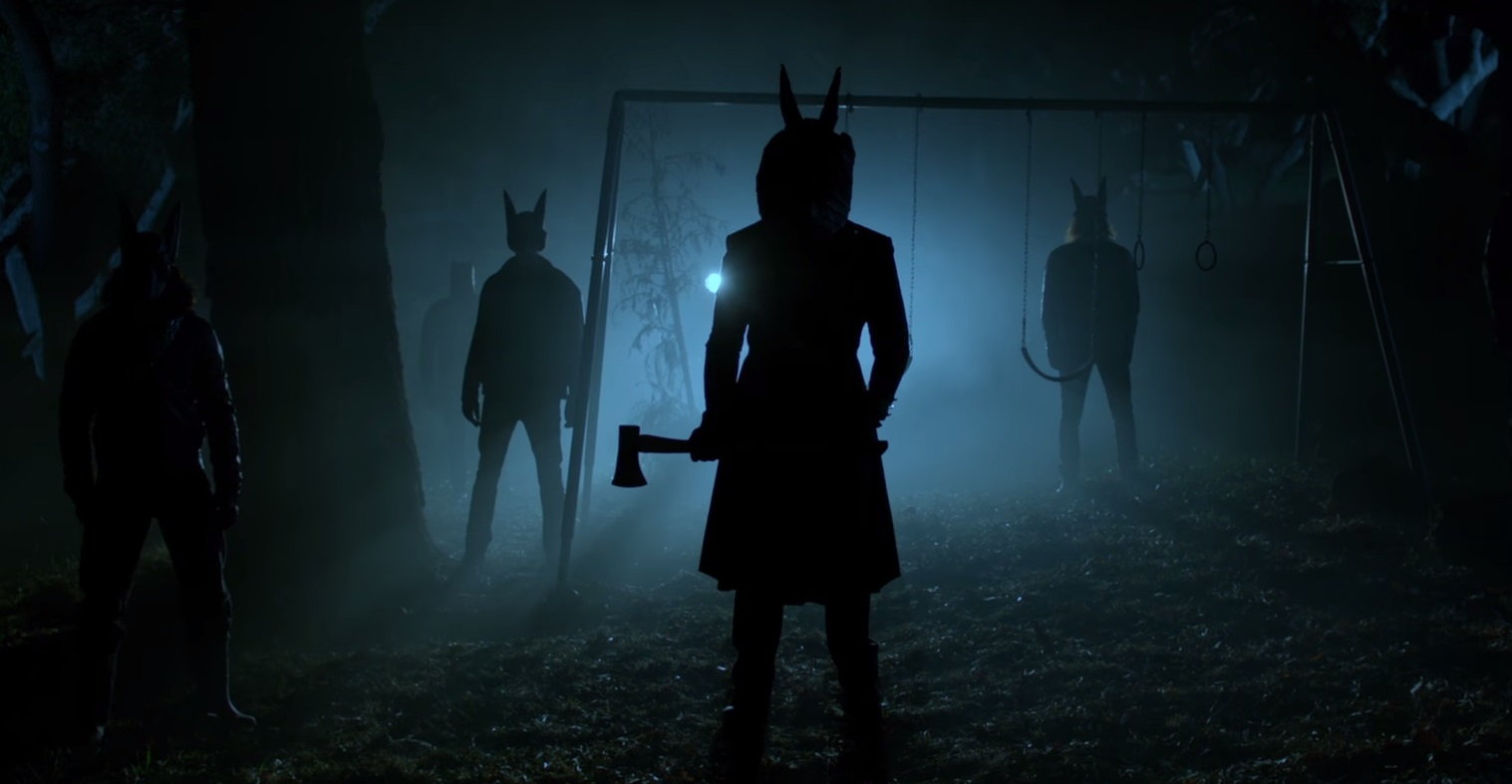 Masked cultists gather outside the house in Jackals (2017)