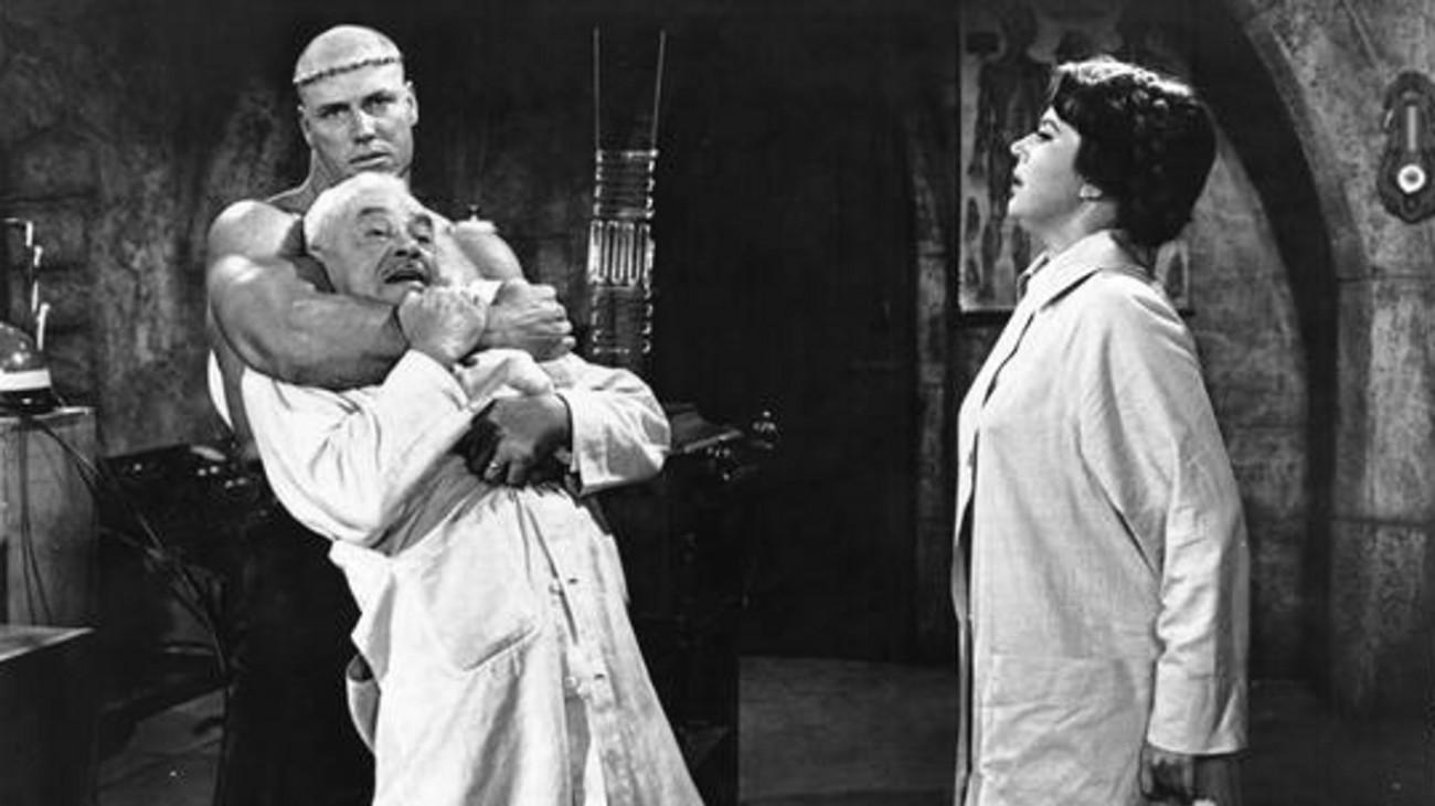 Maria Frankenstein (Narda Onyx) looks on as her monster Hank (Cal Bolder) strangles lab assistant William Fawcett in Jesse James Meets Frankenstein's Daughter (1966)