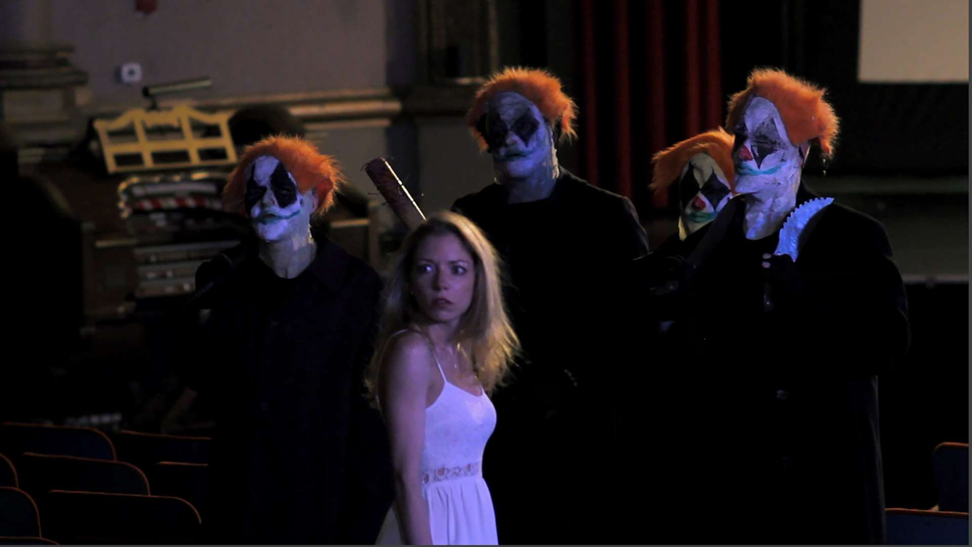 Heroine Aurora (Lacy Marie Meyer) surrounded by ghostly clowns in Joker's Wild (2016)