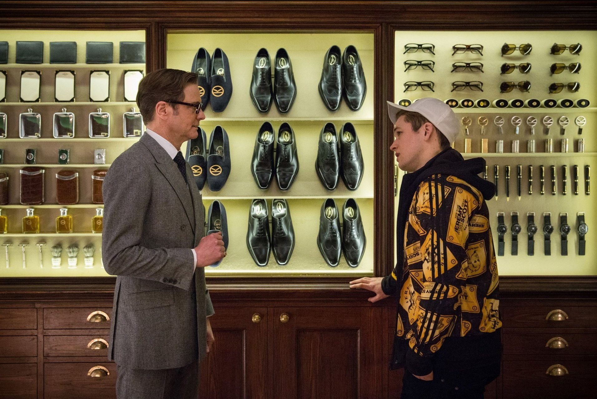 (l to r) Harry Hart (Colin Firth) introduces Eggsy (Taron Egerton) to the Kingsmen in Kingsman: The Secret Service (2015)