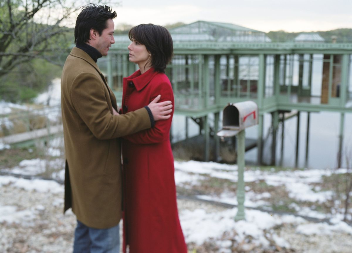 Keanu Reeves and Sandra Bullock with the lake house in the background in The Lake House (2006)