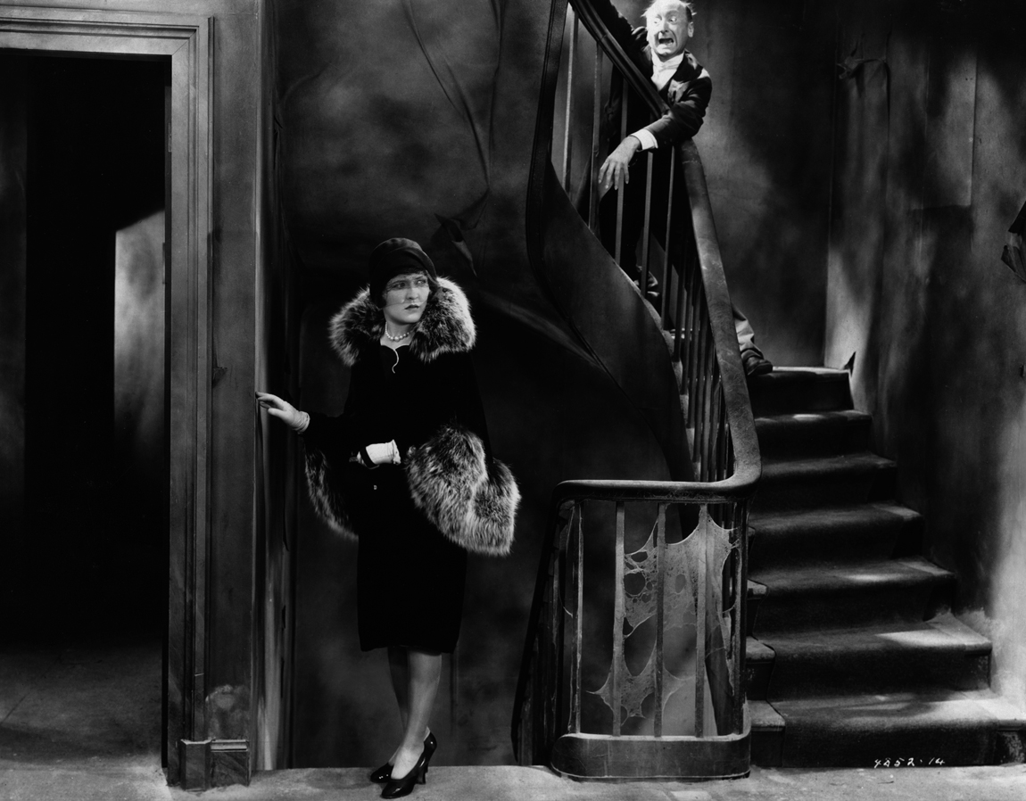 Heroine Laura La Plante while Burr McIntosh lurks at the top of the stairs in The Last Warning (1929)