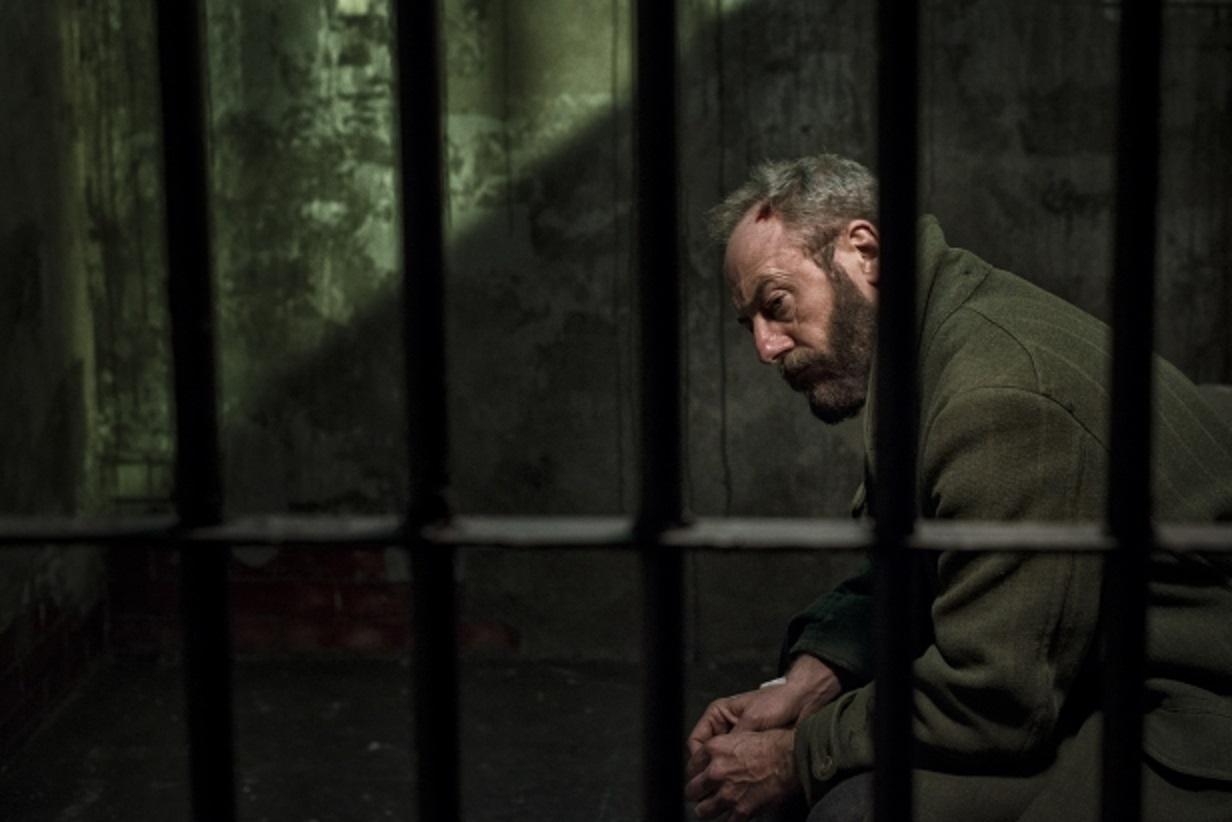 Liam Cunningham, a mysterious stranger manipulating the secrets of a town from within a jail cell in Let Us Prey (2014)