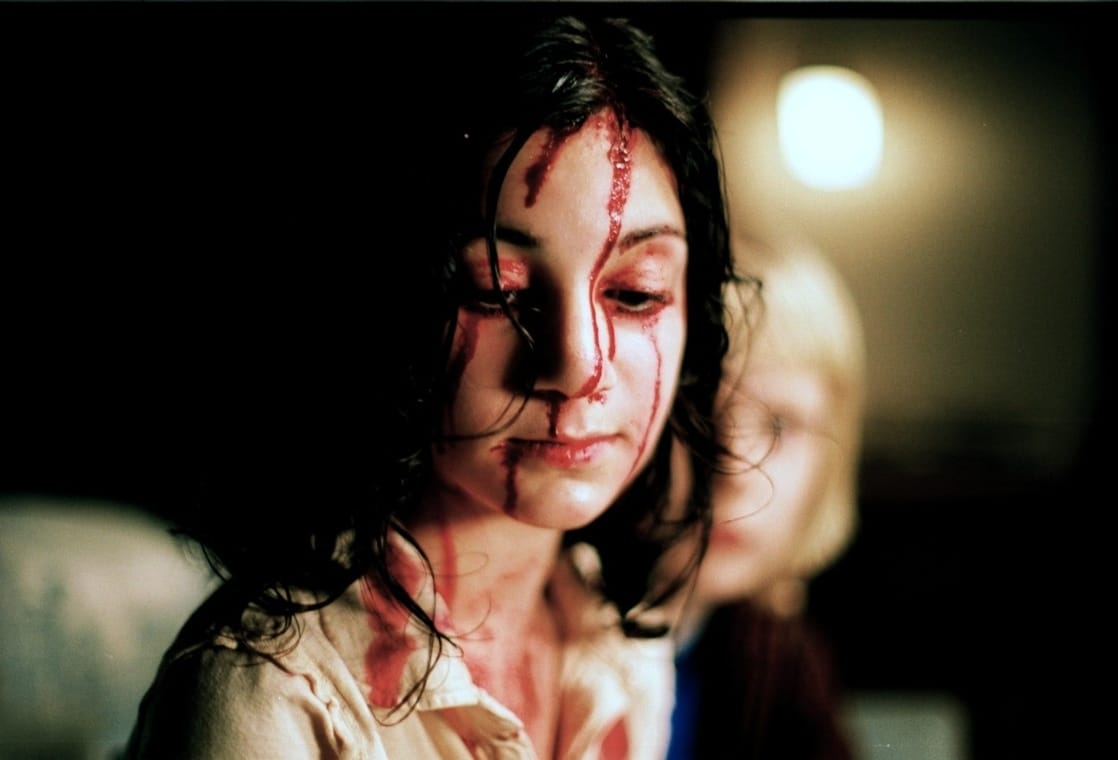 Lina Leandersson as Eli, the mystery girl next door that Oskar befriends in Let the Right One In (2008)
