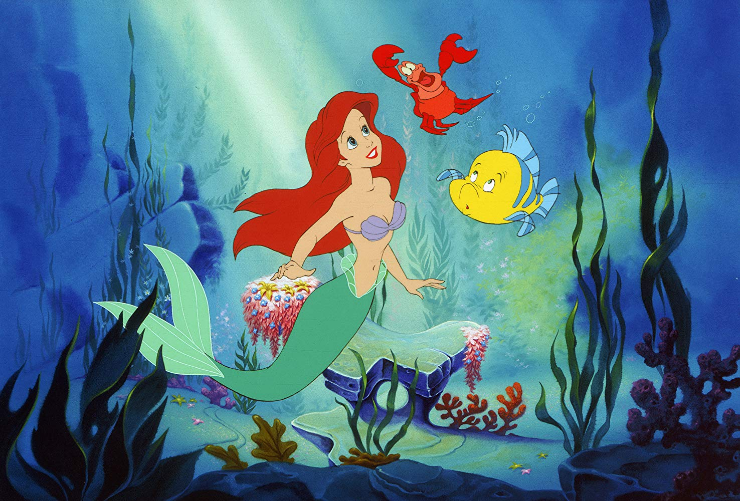 The mermaid Ariel (voiced by Jodi Benson) and her companions (l to r) the crab Sebastian (voiced by Samuel E. Wright) and Flounder (voiced by Jason Marin) in The Little Mermaid (1989)