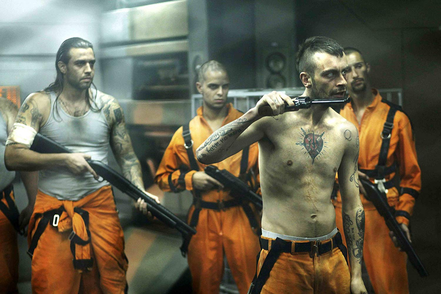 The psychopathic Hydell (Joseph Gilgun) (front) leads the prisoner's revolt in Lockout (2012)