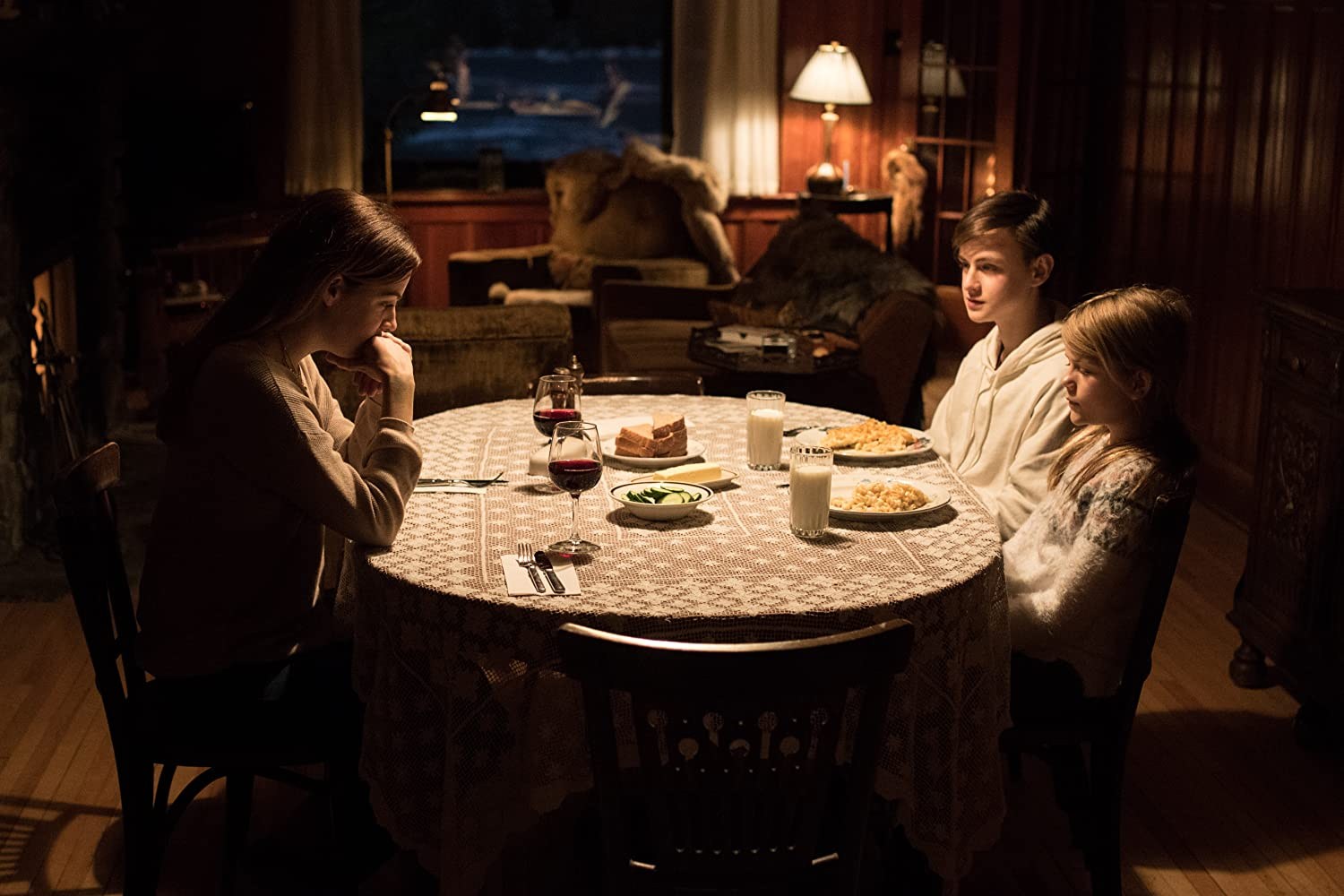 Grace (Riley Keough) sits down to dine with the children (Jaeden Martell and Lia McHugh) in The Lodge (2019)