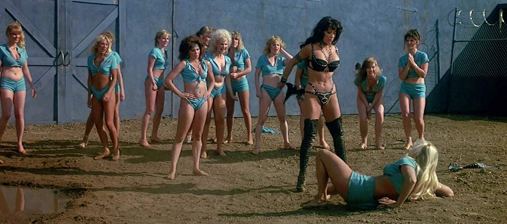 An entirely gratuitous women's prison catight scene with Angelique Pettyjohn (in black leather) standing over Angela Aames in The Lost Empire (1983)