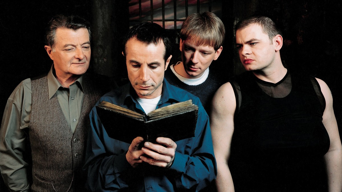 The prisoners - Lasalle (Philippe Laudenbach), Carrere (Gerald Laroche), Paquerette (Dimitri Rataud) and Marcus (Clovis Cornillac) - read from the occult book in Malefique (2002)