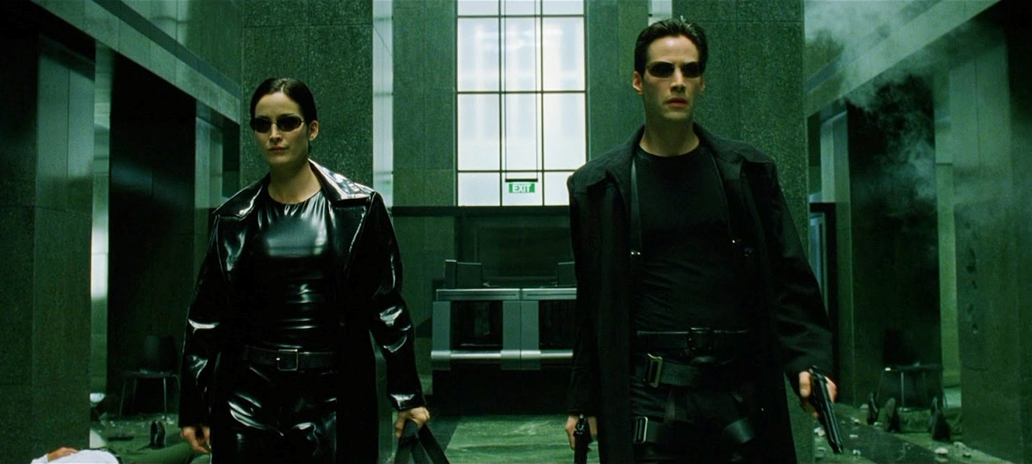 Trinity (Carrie-Anne Moss) and Neo (Keanu Reeves) - the sublime cool of heading into action in black leathers, PVC and shades in The Matrix (1999)