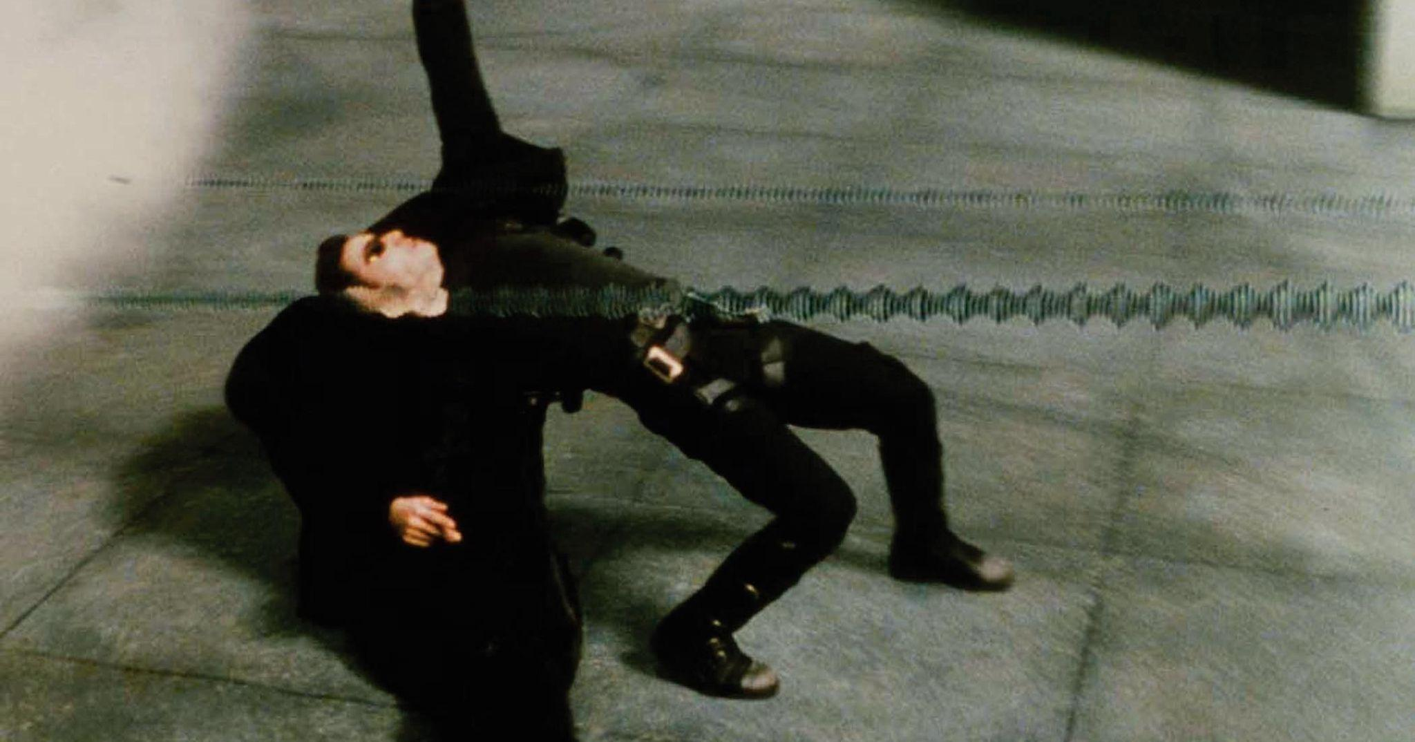 Keanu Reeves ducks bullets in the Bullet Time sequence in The Matrix (1999)